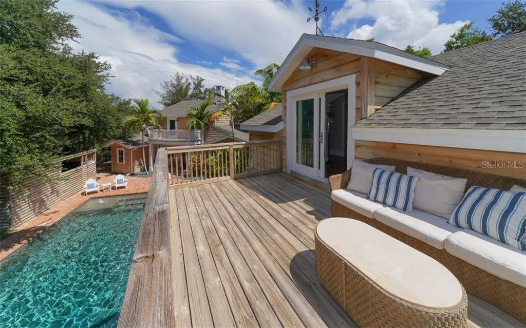 A large outdoor sundeck overlooks the pool and cabana area. - Single Family Home for sale at 138 Island Cir, Sarasota, FL 34242 - MLS Number is A4412265