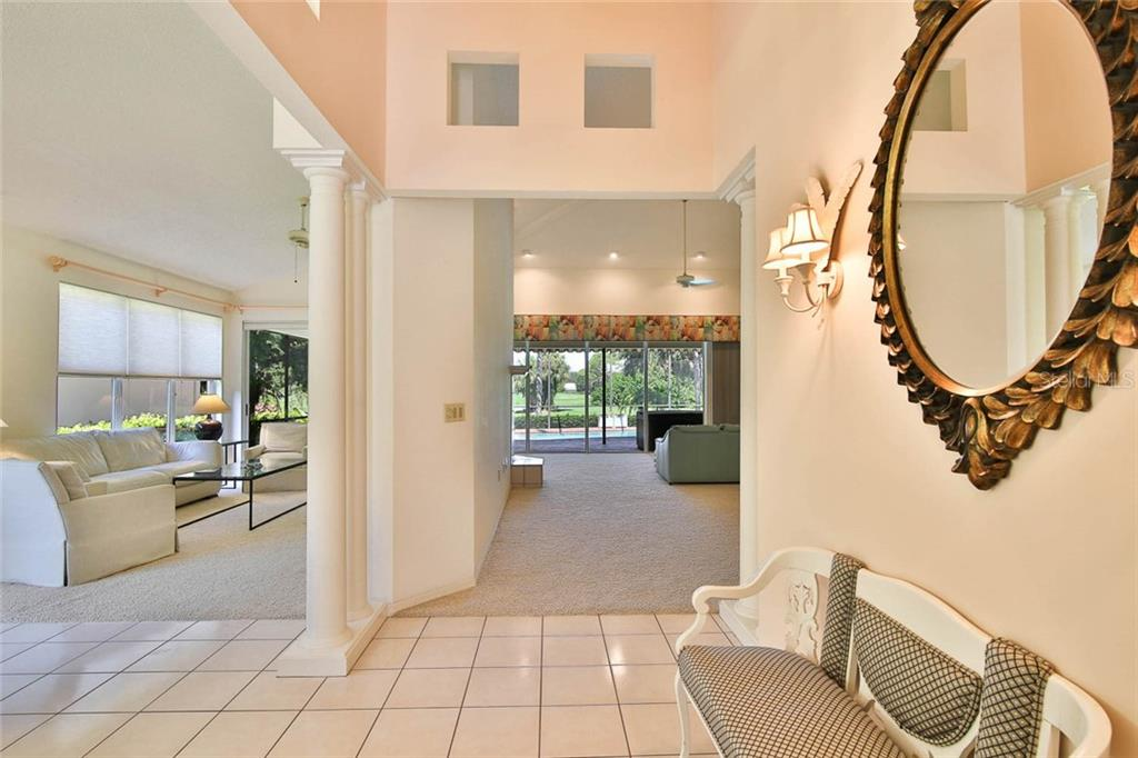 Foyer with views to the pool. - Villa for sale at 7686 Calle Facil, Sarasota, FL 34238 - MLS Number is A4413755