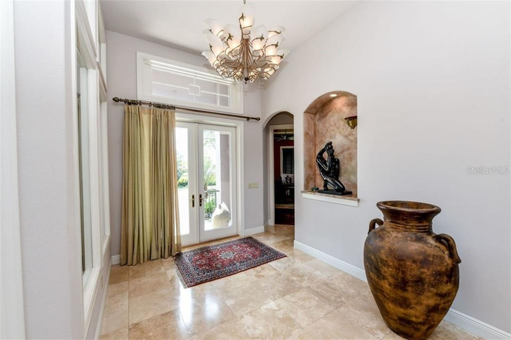 French door entry into foyer.  Travertine flooring. Murano art glass lighting fixture. - Single Family Home for sale at 1483 Tangier Way, Sarasota, FL 34239 - MLS Number is A4414757