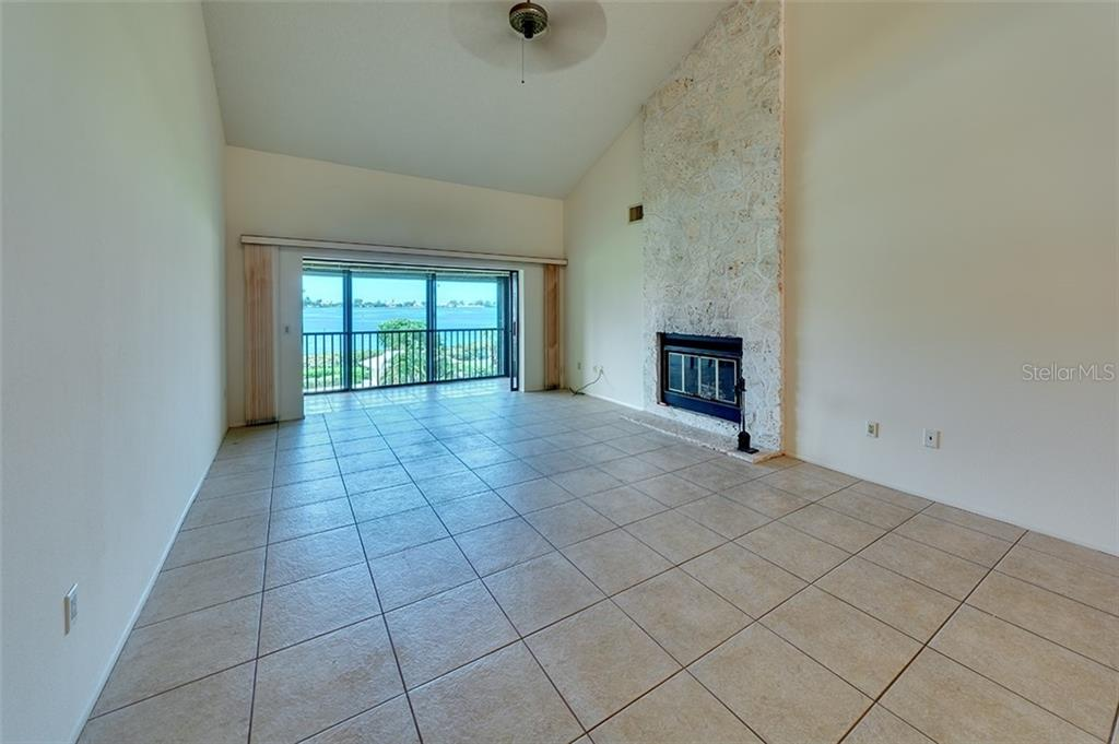 Living Room view with wood burning fireplace. Vaulted ceilings. - Condo for sale at 3920 Mariners Way #323a, Cortez, FL 34215 - MLS Number is A4416115