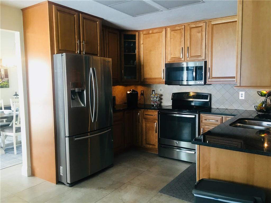 Custom wood cabinet kitchen has stainless appliances, including convection oven, and newer tile floors. - Single Family Home for sale at 1611 82nd St Nw, Bradenton, FL 34209 - MLS Number is A4417607