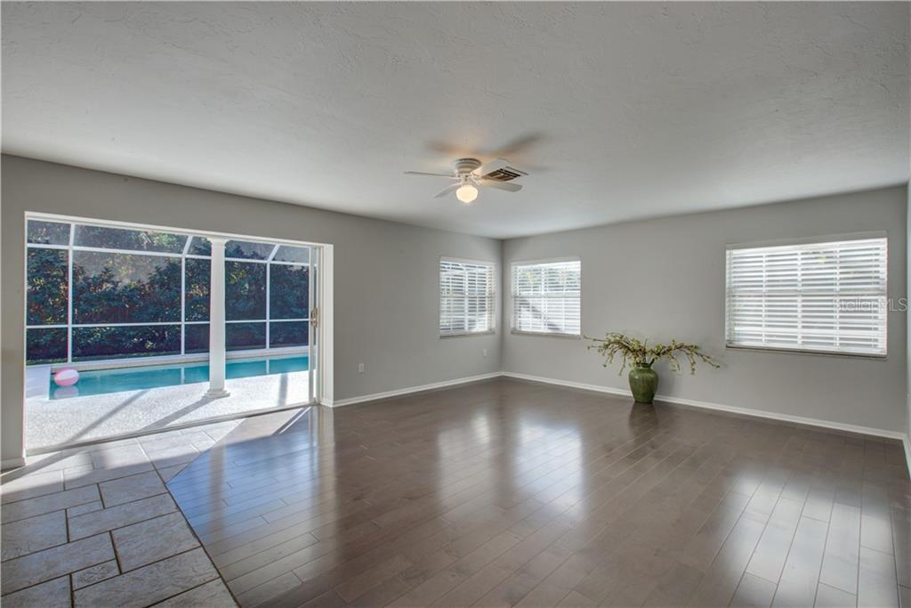 Spacious living room with pocket sliding doors to the enclosed pool - Single Family Home for sale at 5167 Kestral Park Ln, Sarasota, FL 34231 - MLS Number is A4421162