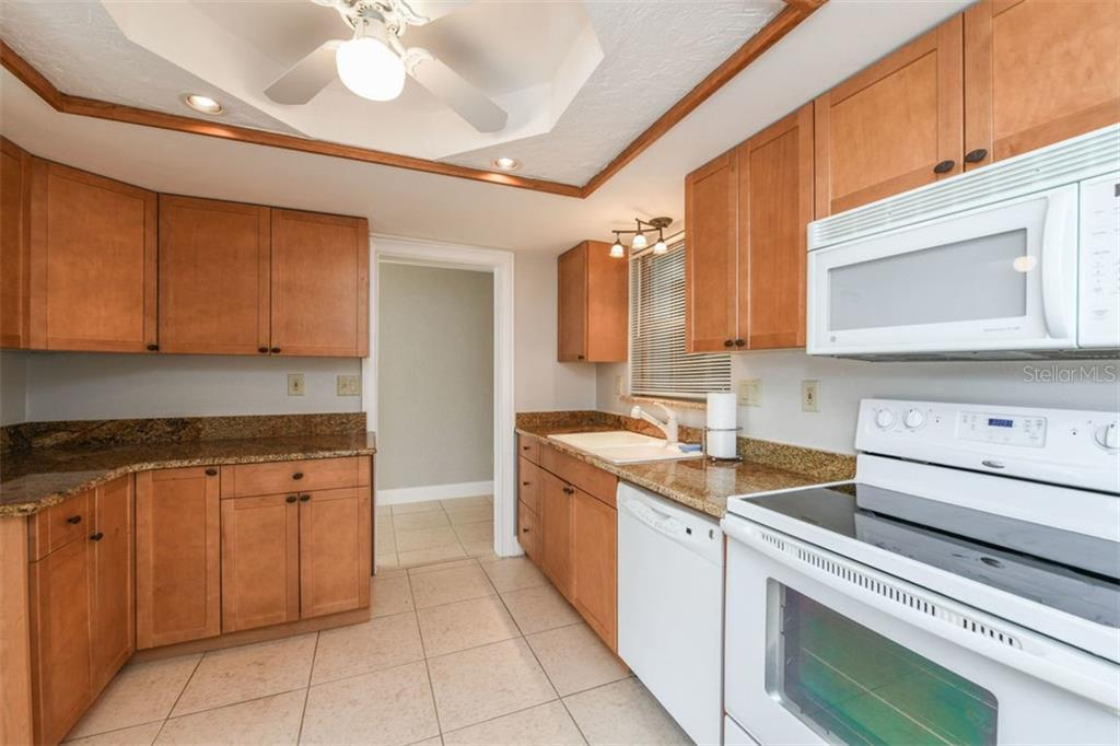 Kitchen with granite countertops. - Villa for sale at 3434 Medford Ln #1110, Sarasota, FL 34239 - MLS Number is A4422897