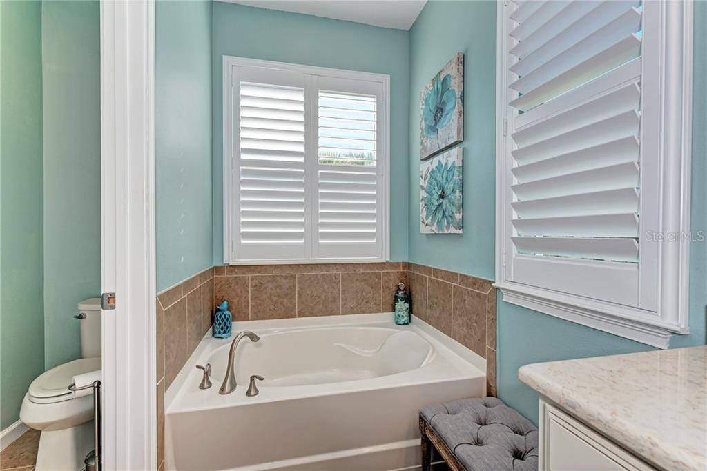 A bathroom with natural lighting is perfect for putting on makeup, and these plantation shutters provide you with the perfect amount of lighting or the privacy that you'll need! - Single Family Home for sale at 5260 Bentgrass Way, Bradenton, FL 34211 - MLS Number is A4424484