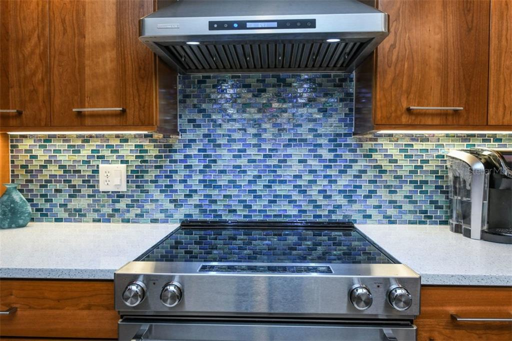 Translucent glass tile backsplash in shimmering shades of blue is carried throughout the kitchen, dining room, and even the tile trim in both bathrooms. - Condo for sale at 225 Hourglass Way #208, Sarasota, FL 34242 - MLS Number is A4425323