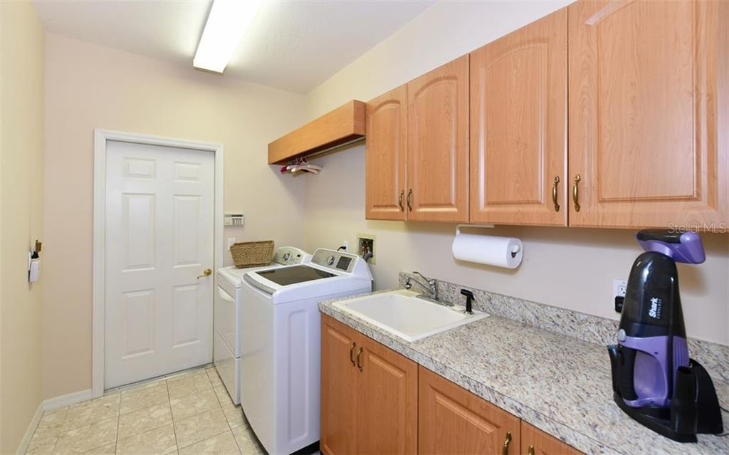 Laundry room between kitchen and garage - Single Family Home for sale at 7867 Estancia Way, Sarasota, FL 34238 - MLS Number is A4426528