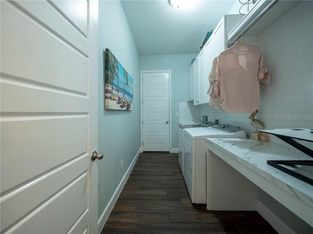 Oversized laundry with subway tile backsplash, 42 inch upper cabinets, folding/ironing desk, and hanging rod - Single Family Home for sale at 3611 4th Ave Ne, Bradenton, FL 34208 - MLS Number is A4426978
