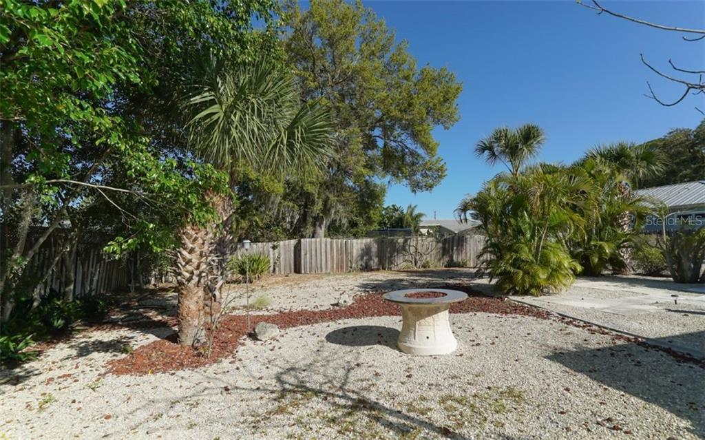 Large fenced backyard with tropical foliage. - Single Family Home for sale at 310 Bayview Pkwy, Nokomis, FL 34275 - MLS Number is A4430065