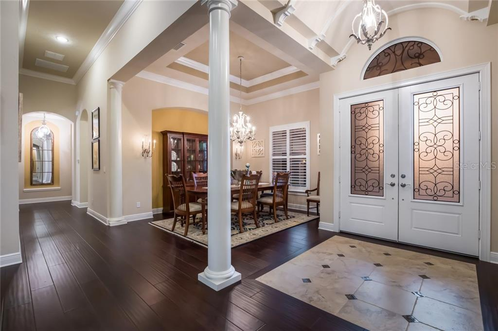Walk into the foyer and you are immediately greeted by the 10-14 foot ceilings and the formal dining room. - Single Family Home for sale at 19432 Newlane Pl, Bradenton, FL 34202 - MLS Number is A4432094
