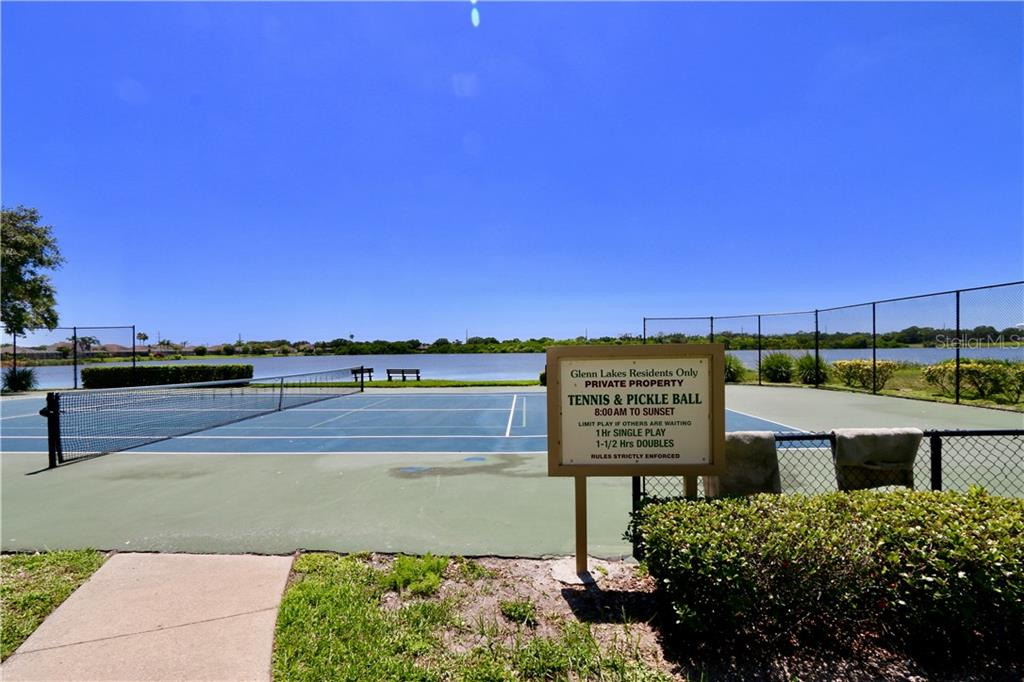 Community tennis and pickle ball court with lake in background - Single Family Home for sale at 5082 47th St W, Bradenton, FL 34210 - MLS Number is A4435806