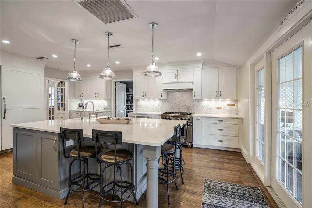 Gorgeous kitchen with quartz counters, large center island, Sub-Zero fridge/freezer that blend with the cabinetry. - Single Family Home for sale at 590 Bayshore Dr, Terra Ceia, FL 34250 - MLS Number is A4437024