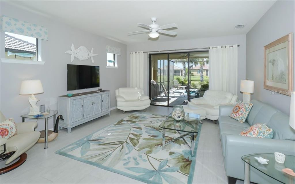 Living Room with sliders to Lanai - Single Family Home for sale at 13337 Pacchio St, Venice, FL 34293 - MLS Number is A4437569