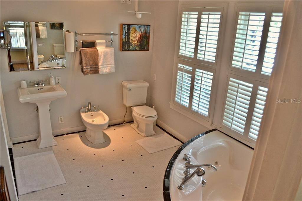 Well appointed master bathroom with a large walk-in closet, commode, bidet, whirlpool jet tub, plantation shutters for privacy, and a large shower. - Single Family Home for sale at 813 Hudson Ave, Sarasota, FL 34236 - MLS Number is A4437601