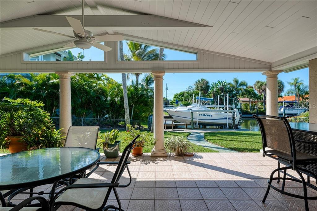 Covered outdoor living space with walkway to the canal and boat lift - Single Family Home for sale at 602 Baronet Ln, Holmes Beach, FL 34217 - MLS Number is A4447974