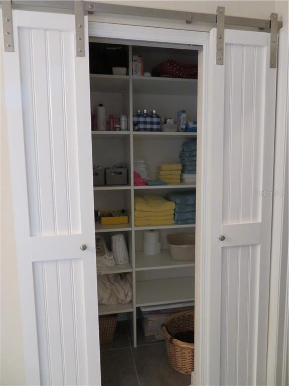 Barn doors open in center. Linen closet with custom shelving - Single Family Home for sale at 5727 Arbor Wood Ct, Bradenton, FL 34203 - MLS Number is A4448047