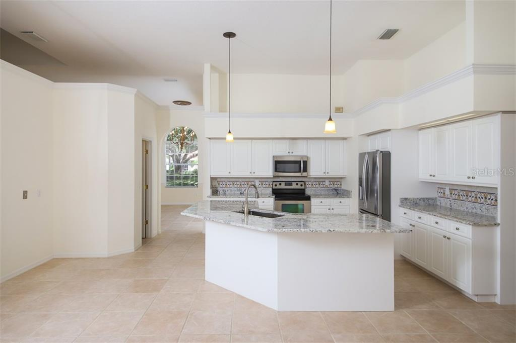A large kitchen with lots of storage and workspace opens directly to the family room - Single Family Home for sale at 6620 Hunter Combe Xing, University Park, FL 34201 - MLS Number is A4450282