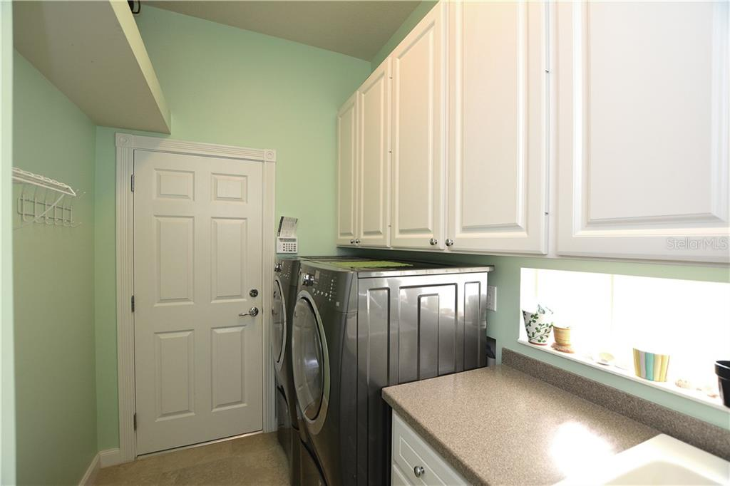 Laundry room with utility sink and extra storage. - Single Family Home for sale at 5799 Benevento Dr, Sarasota, FL 34238 - MLS Number is A4450677