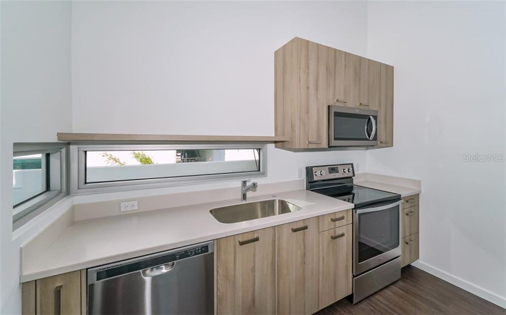This modern kitchen is tastefully appointed with a floating shelf accented by elongated windows allowing natural lighting to fill the room. - Condo for sale at 1350 5th Street #104, Sarasota, FL 34236 - MLS Number is A4463799
