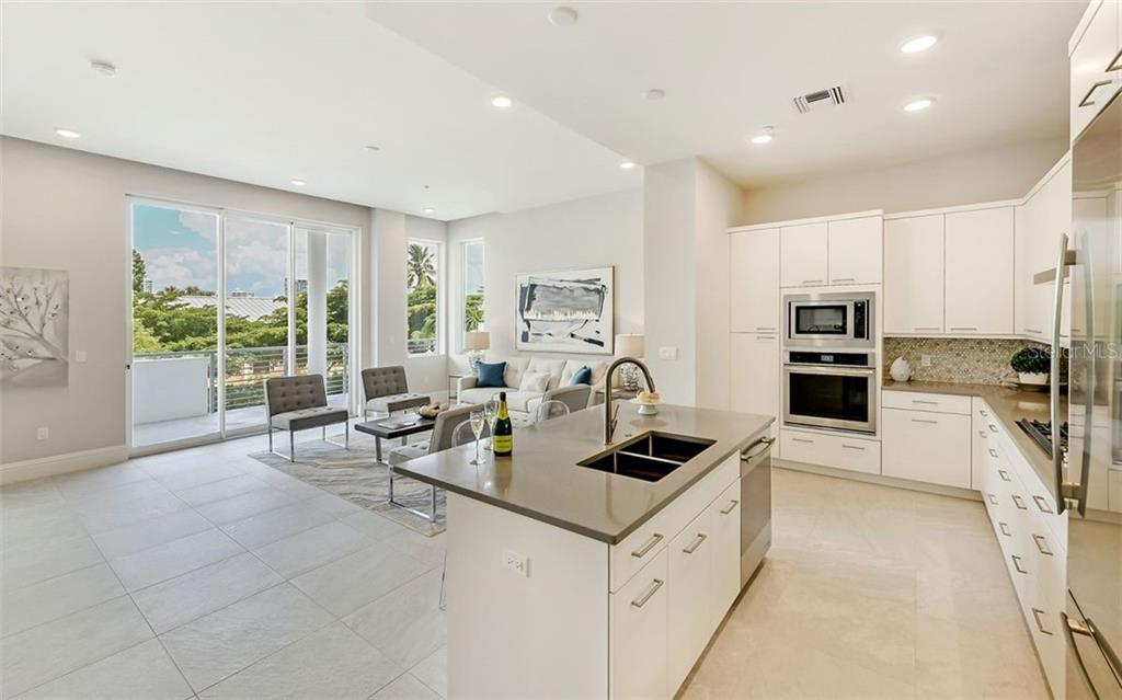 The chef's kitchen is complete with gas cook-top, Eurotech cabinetry, quartz countertops and premium appliances. - Condo for sale at 609 Golden Gate Pt #201, Sarasota, FL 34236 - MLS Number is A4468917