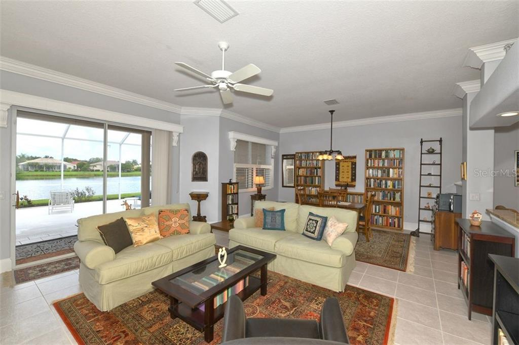 Living Room/Dining Room, sliders to the view! Crown molding, valances and door trim - Villa for sale at 4590 Samoset Dr, Sarasota, FL 34241 - MLS Number is A4471881