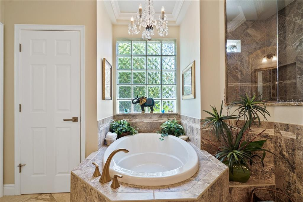 beautiful tub with gold fixtures surrounded by gorgeous tile - Single Family Home for sale at 1907 Clematis St, Sarasota, FL 34239 - MLS Number is A4474600