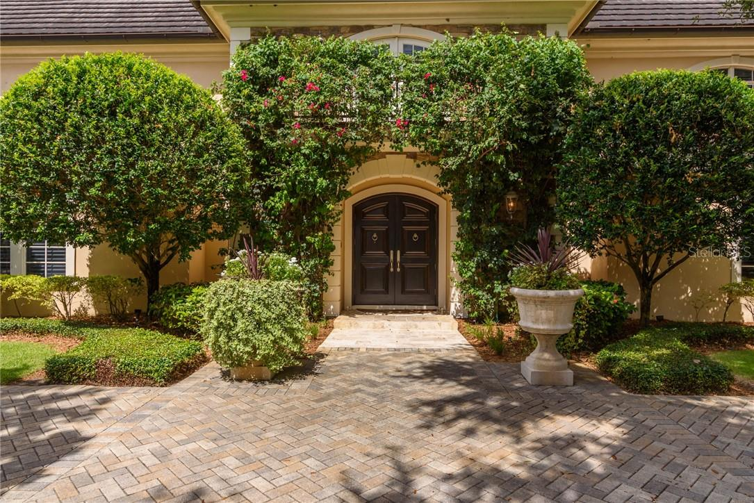 Dramatic front entry features flowering bougainvillea and other tropical foliage. - Single Family Home for sale at 1807 Oleander St, Sarasota, FL 34239 - MLS Number is A4475067