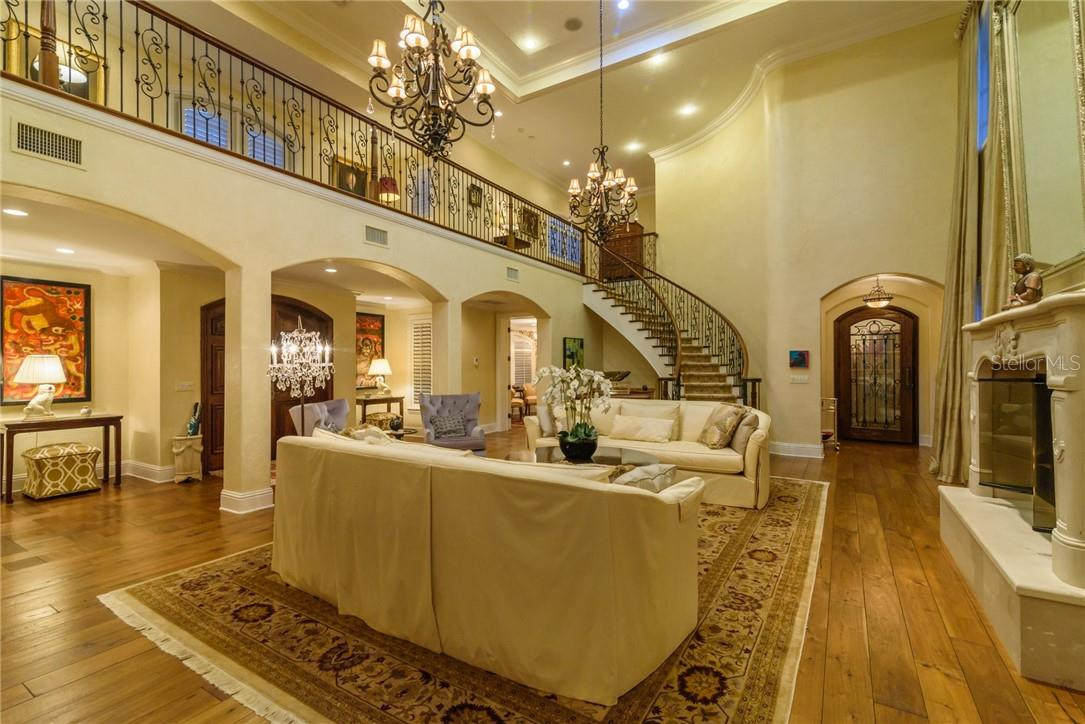 The two story living room with gas fireplace is graced by the winding staircase and custom wrought iron railing overlooking the space as well as Grand Foyer and Entry door beyond. - Single Family Home for sale at 1807 Oleander St, Sarasota, FL 34239 - MLS Number is A4475067