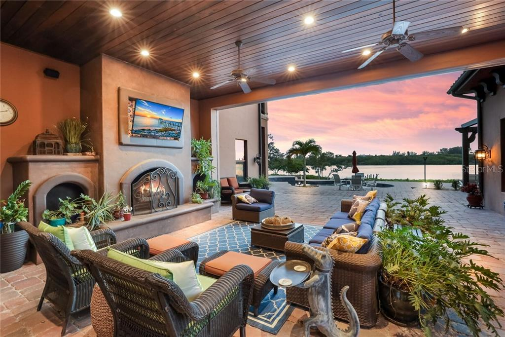 Loggia with a fireplace and views to the water. Screens pocket in the ceiling to create a fully screened in room. - Single Family Home for sale at 4925 Topsail Dr, Nokomis, FL 34275 - MLS Number is A4475116