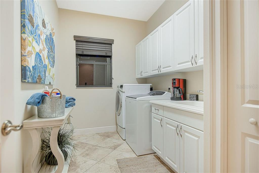 Large laundry room with cabinetry, utility sink, and closet. - Single Family Home for sale at 14507 Leopard Crk, Lakewood Ranch, FL 34202 - MLS Number is A4478709