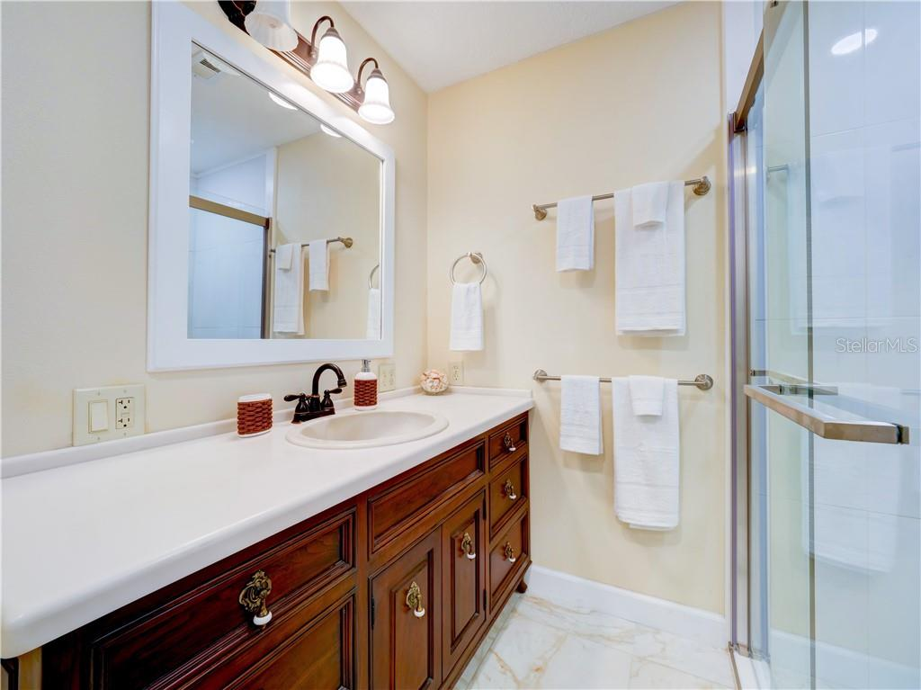 Master bathroom features a beautiful custom cherry vanity with solid surface counter tops and a shower. - Single Family Home for sale at 2408 Riverside Dr E, Bradenton, FL 34208 - MLS Number is A4480609