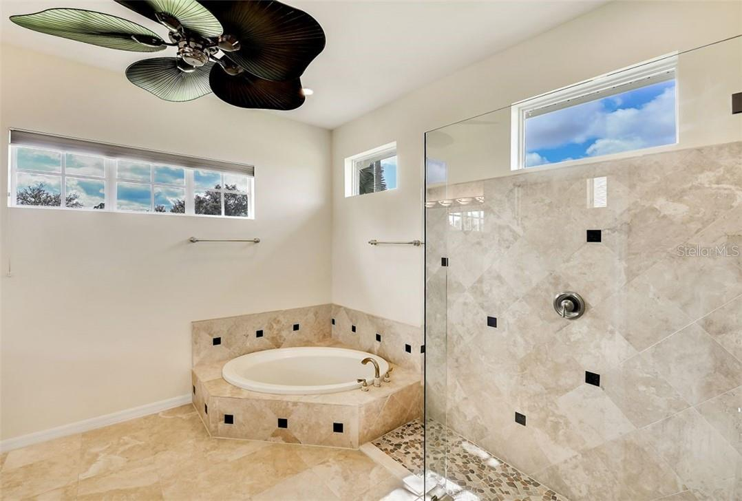 Owners bath with garden tub, pebble shower flooring and seamless panels - Single Family Home for sale at 7832 Panther Ridge Trl, Bradenton, FL 34202 - MLS Number is A4483837