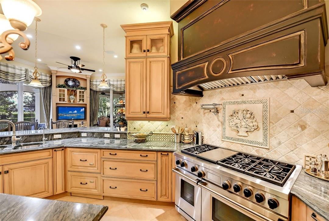 The travertine custom backsplash with a harvest relief in stone to inspire any great chef to create. - Single Family Home for sale at 8263 Archers Ct, Sarasota, FL 34240 - MLS Number is A4483993