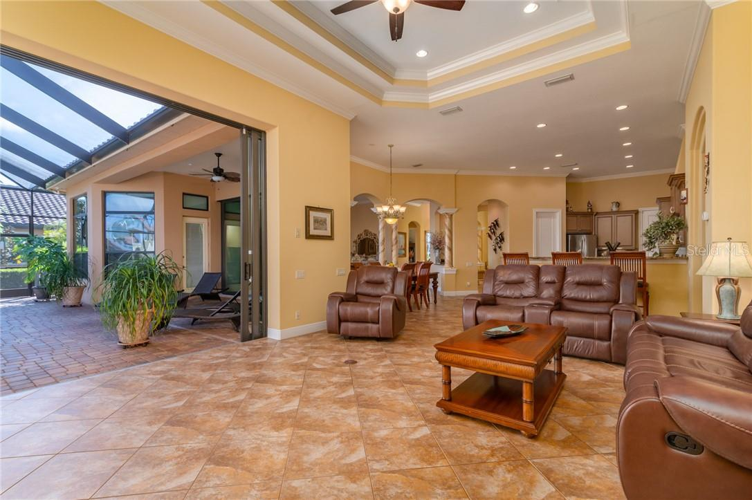 The Great Room, with disappearing Sliding Glass Doors (impact glass) and views of the expansive water. - Single Family Home for sale at 11720 Rive Isle Run, Parrish, FL 34219 - MLS Number is A4486302