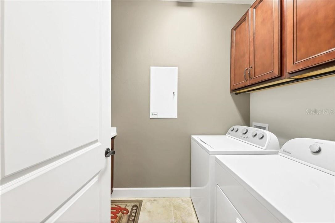Large laundry room with over laundry machine storage and extra base cabinets with laundry tub. - Single Family Home for sale at 11713 Blue Hill Trl, Bradenton, FL 34211 - MLS Number is A4490622