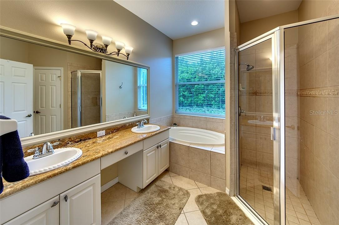 Relaxing En-Suite Features Granite Counters, China Sinks and Framed Mirrors - Single Family Home for sale at 7739 Us Open Loop, Lakewood Ranch, FL 34202 - MLS Number is A4494156