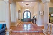 Main Entry Foyer - Gorgeous custom doors and rich Mexican tile. - Single Family Home for sale at 8130 Perry Maxwell Cir, Sarasota, FL 34240 - MLS Number is A4175735