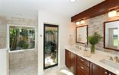 Master ensuite with tiled shower, dual sinks and garden view. - Single Family Home for sale at 5122 Willow Leaf Dr, Sarasota, FL 34241 - MLS Number is A4209555