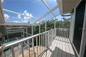 From the 3rd floor deck, overlooking the 2nd floor deck and 1st floor deck of the screened in pool with the canal just beyond. - Single Family Home for sale at 660 Marbury Ln, Longboat Key, FL 34228 - MLS Number is A4415911