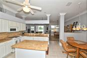 The kitchen,, nook and out to the dining room.  AND the view. - Villa for sale at 4590 Samoset Dr, Sarasota, FL 34241 - MLS Number is A4471881
