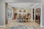 The dining room features a fabulous stacked stone accent wall, designer chandelier and premium tile. - Single Family Home for sale at 11713 Blue Hill Trl, Bradenton, FL 34211 - MLS Number is A4490622
