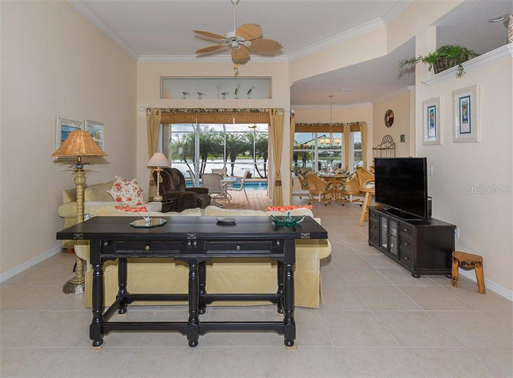 Living room with slider to lanai - Single Family Home for sale at 627 Lakescene Dr, Venice, FL 34293 - MLS Number is N6103268