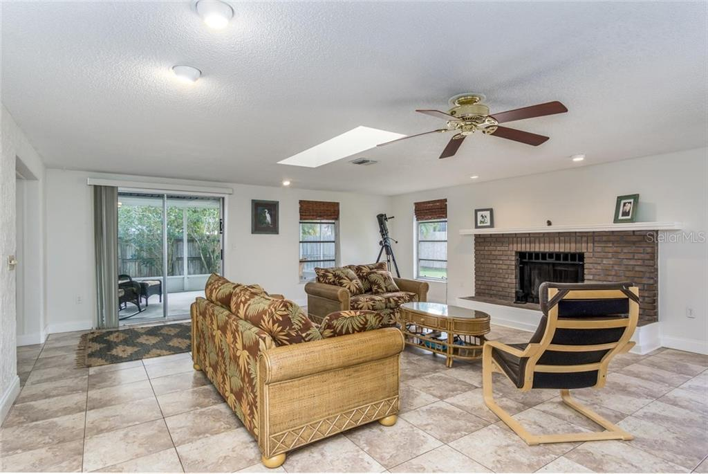 huge family room, has a sky light, tile floors, wood burning fireplace, and sliding glass door to covered screen lanai. - Single Family Home for sale at 3656 Clematis Rd, Venice, FL 34293 - MLS Number is N6103558