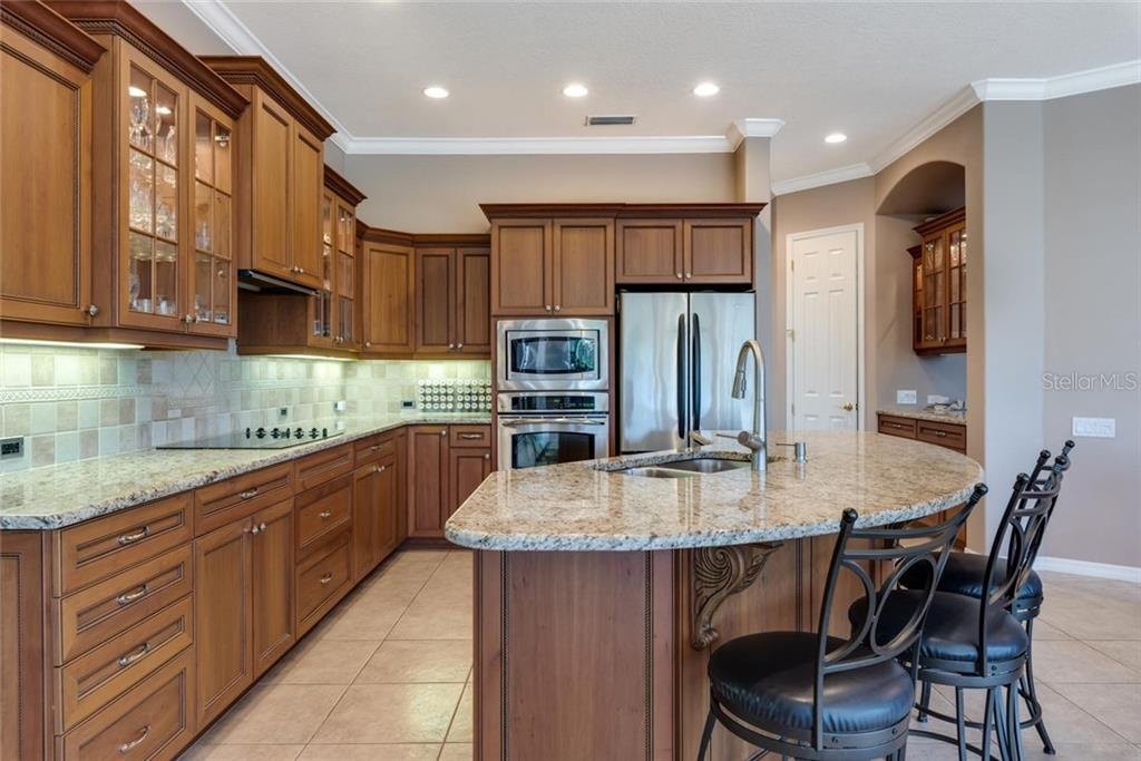 Kitchen with Cherry cabinets, royal rope molding, granite counters and pass through to the dining room - Single Family Home for sale at 821 Adonis Pl, Venice, FL 34292 - MLS Number is N6104303