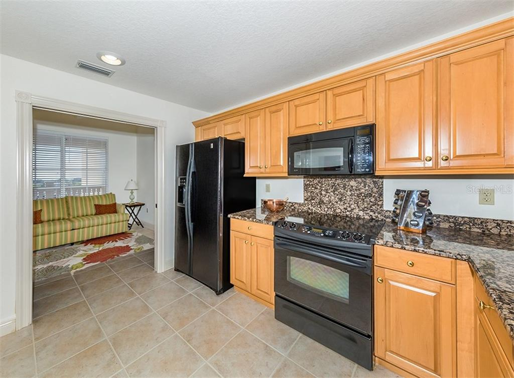 Kitchen with pocket doors to den - Condo for sale at 147 Tampa Ave E #902, Venice, FL 34285 - MLS Number is N6104823