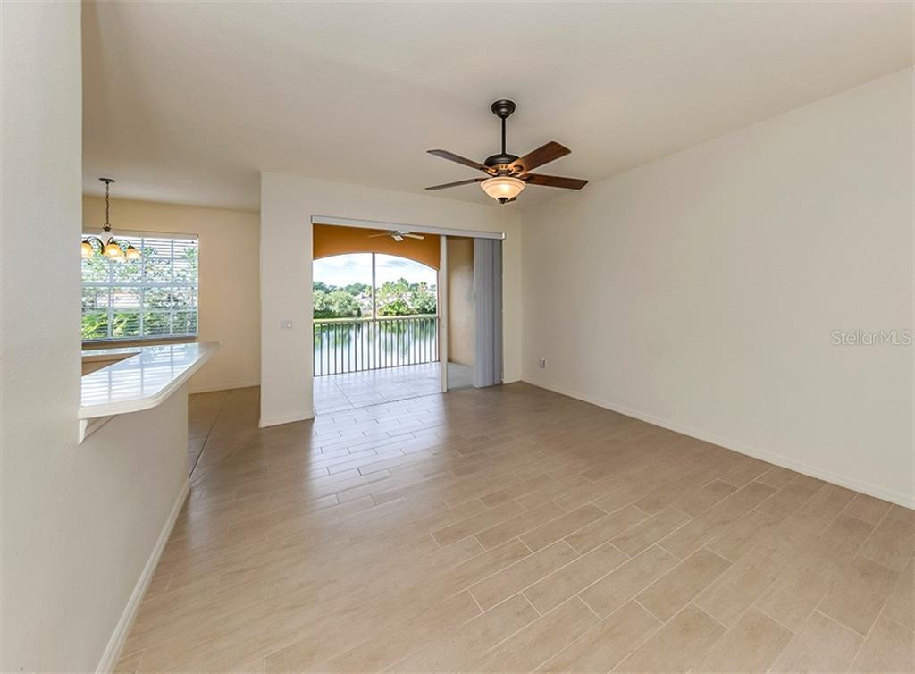 Living room with slider to lanai - Condo for sale at 1761 Auburn Lakes Dr #22, Venice, FL 34292 - MLS Number is N6106204