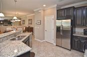 Kitchen to dining room - Single Family Home for sale at 9124 Coachman Dr, Venice, FL 34293 - MLS Number is N5914408
