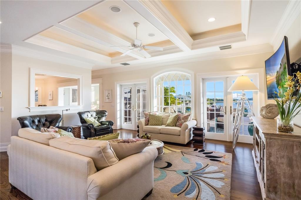 Sunlit living room with double French doors opening to large patio overlooking the water - Single Family Home for sale at 1600 E Railroad Ave, Boca Grande, FL 33921 - MLS Number is D6108744