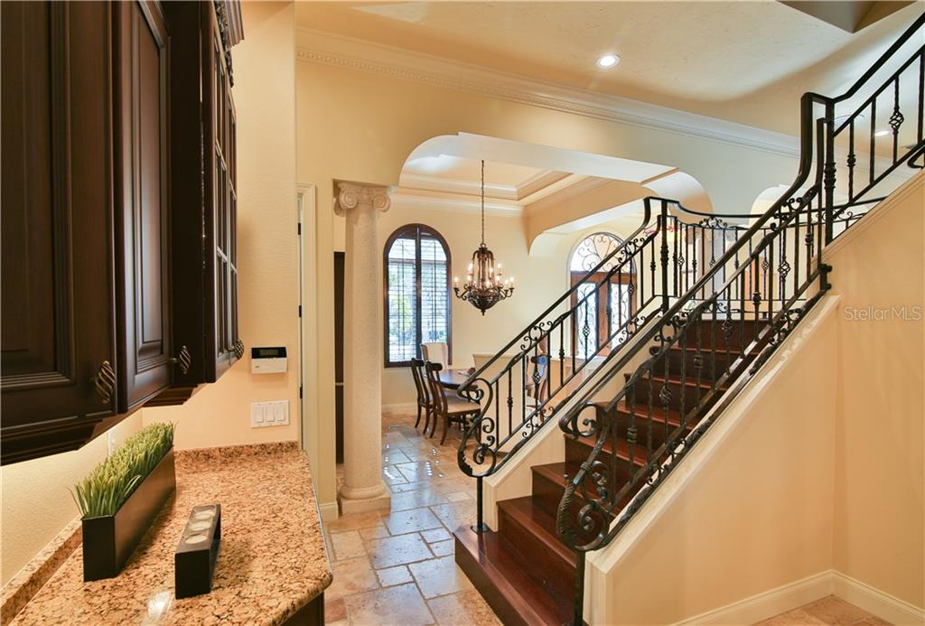 Butlers pantry area has under counter wine chiller; solid wood stairway with decorative scroll ironwork takes you to the 2nd level. - Single Family Home for sale at 8365 Catamaran Cir, Lakewood Ranch, FL 34202 - MLS Number is A4187448