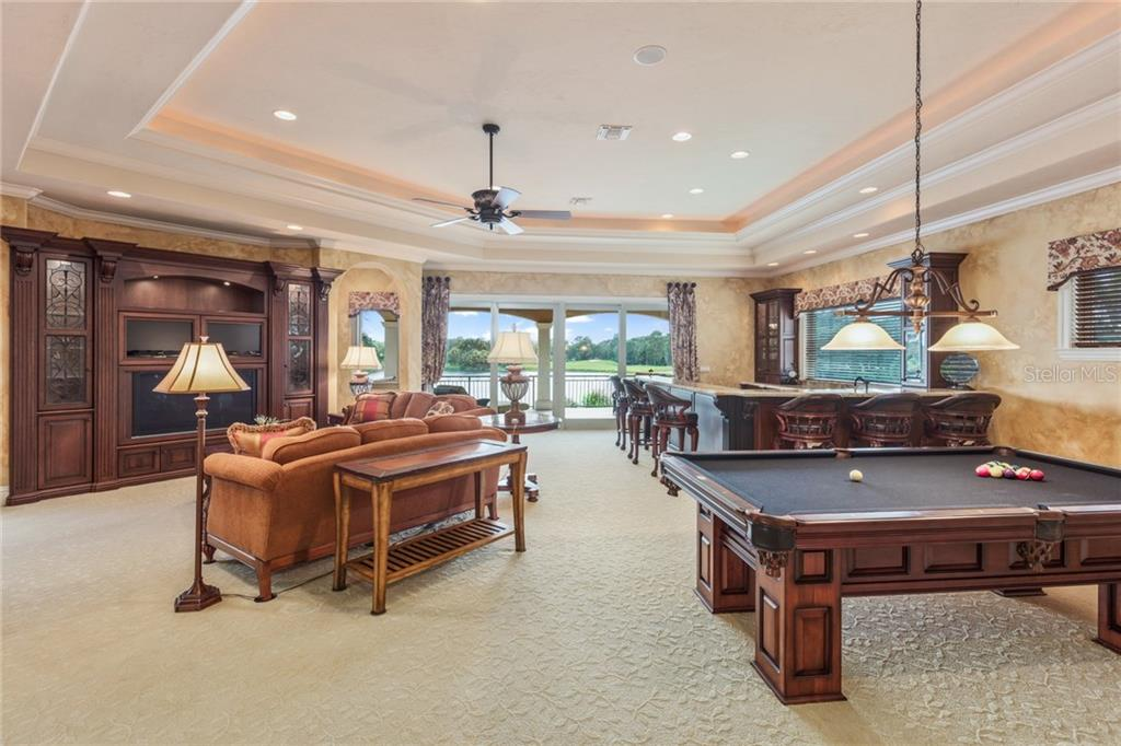 Welcome to the upstairs game room and bar large enough to host any size event!  This game area has a beautiful built-in entertainment system, space for your billiard table and a private screened balcony to enjoy the phenomenal lake views! - Single Family Home for sale at 7320 Barclay Ct, University Park, FL 34201 - MLS Number is A4200908