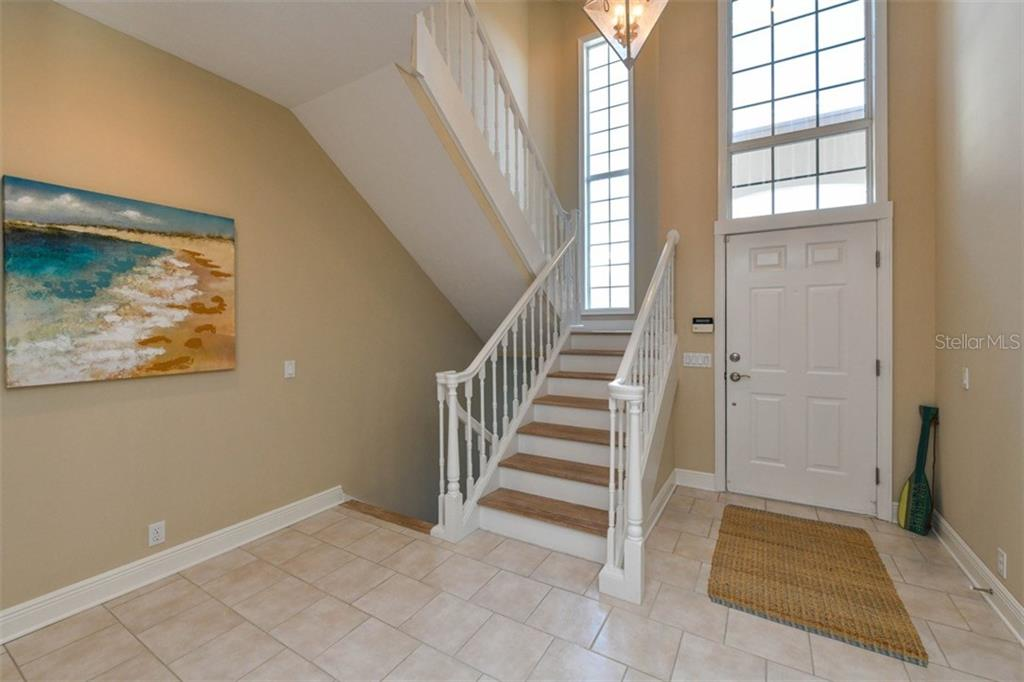 Entry with brick/offset tile flooring 2 story windows, and lovely staircase. - Single Family Home for sale at 3947 Somerset Dr, Sarasota, FL 34242 - MLS Number is A4201541